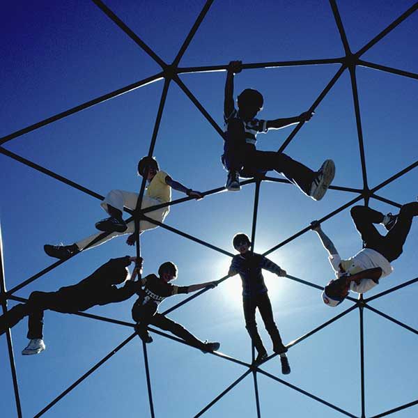 children climbing on playground equipment,  backlit.