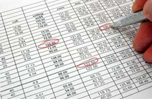 person marking errors in billing sheet.