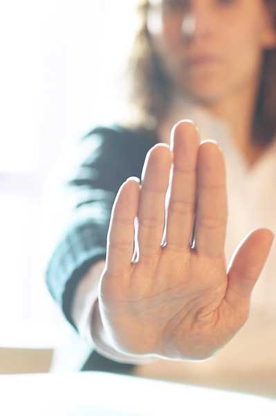 woman holding hand forward, palm outward, indicating no or refusal.