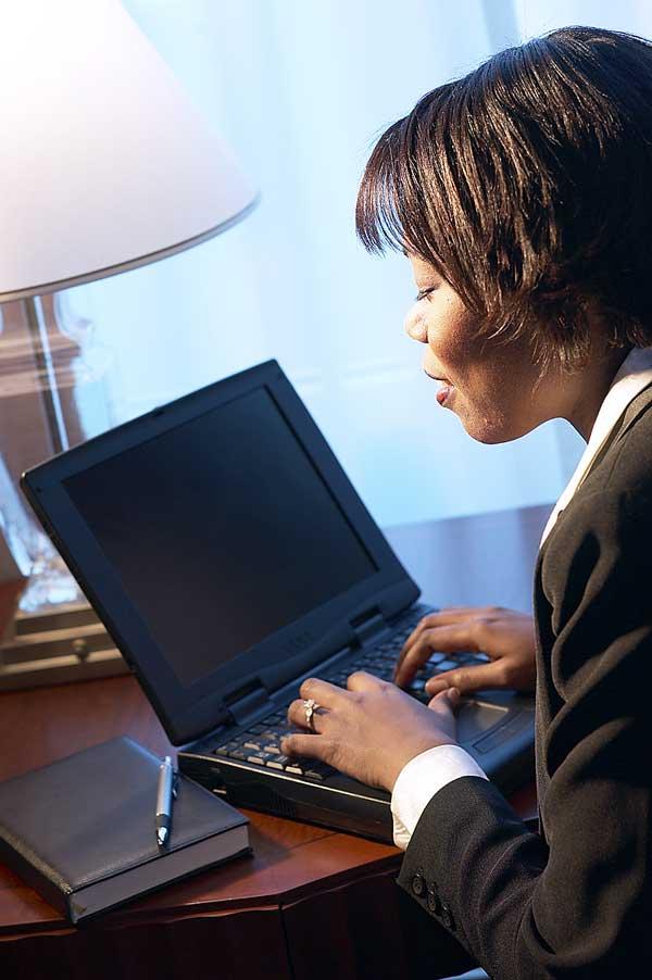 Woman on computer reading handbook.